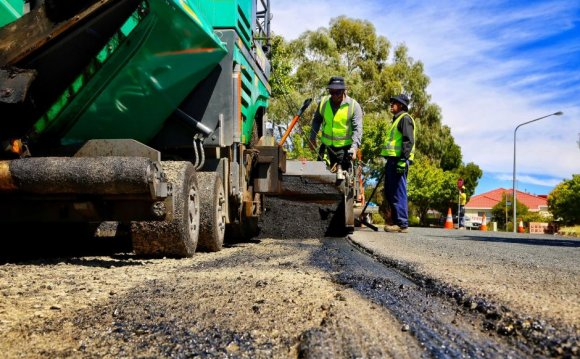 Road workers lay asphalt on a