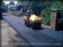 an innovative new asphalt driveway being set up plus the roller compacting the asphalt while it's hot