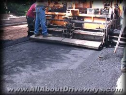 an asphalt paving machine laying a fresh asphalt driveway