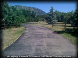 an older asphalt driveway therefore the effects of aging and oxidization from the sunlight